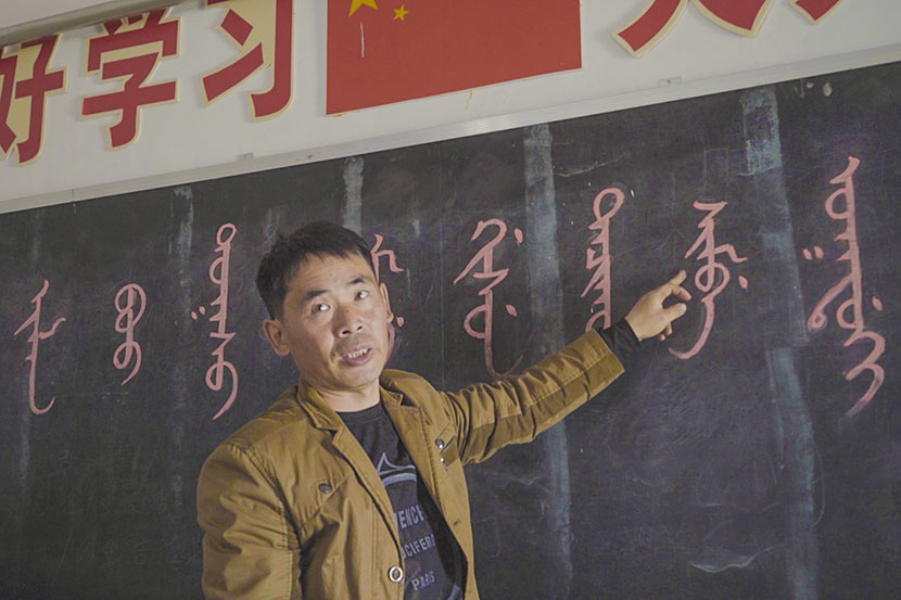 Shi Junguang talks pupils at the Sanjiazi Manchu Elementary School through a Manchu phrase, which reads 'Sanjiazi Manchu Elementary School welcomes you,' Qiqihar, Heilongjiang province, May 10, 2017. Tang Xiaolan/Sixth Tone