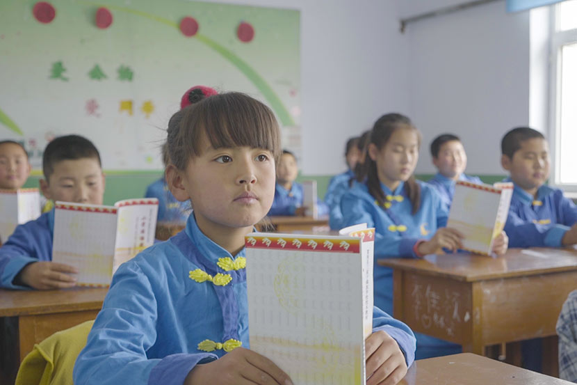 Students read from textbooks during a Manchu class at Sanjiazi Manchu Elementary School in Sanjiazi Village, Qiqihar, Heilongjiang province, May 10, 2017. Tang Xiaolan/Sixth Tone
