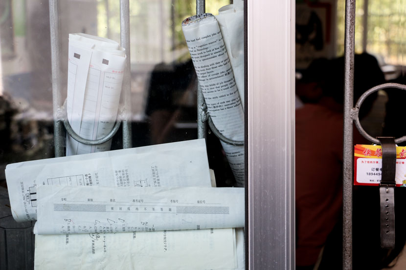 Rolled-up exam papers are displayed in the bars of a school window in Guanzhuang Township, Hunan province, May 17, 2017. Cai Yiwen/Sixth Tone