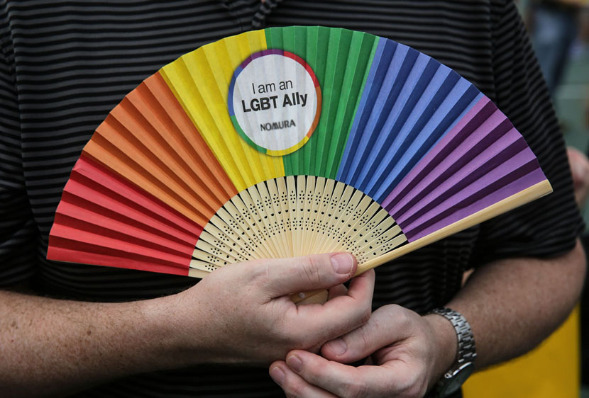 A man holds a rainbow-colored fan during the annual gay pride parade in Hong Kong, Nov. 6, 2015. Isaac Lawrence/VCG