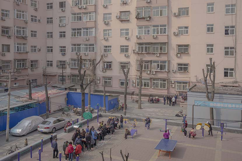 Neighborhood residents play board games in the courtyard behind the Anhua Building in Beijing, March 21, 2018. Wu Yue/Sixth Tone