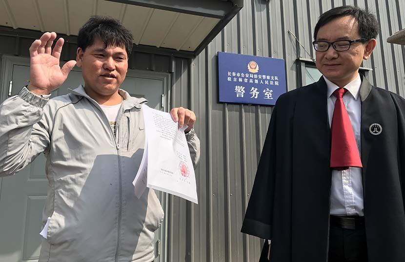 Liu Zhonglin holds the Jilin High People's Court's verdict of innocence in Changchun, Jilin province, April 20, 2018. Song Jiangxuan for Sixth Tone