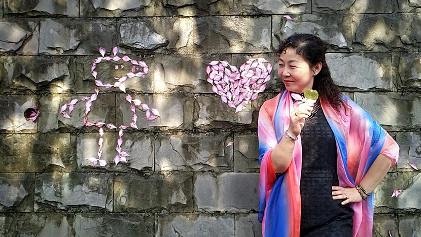 A woman poses for a photo next to an outline of Peppa Pig made from flower petals at a park in Liuzhou, Guangxi Zhuang Autonomous Region, April 1, 2018. Zhang Cunli/IC
