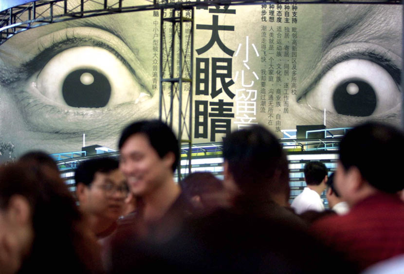 People walk past a real estate advertisement during a fair in Hangzhou, Zhejiang province, June 19, 2003. Wu Huang/VCG