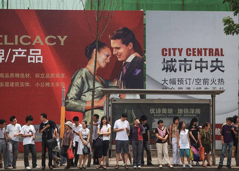 People waits for buses in front of a real state advertisement in Shenyang, Liaoning province, June 23, 2008. Su Luzhang/IC