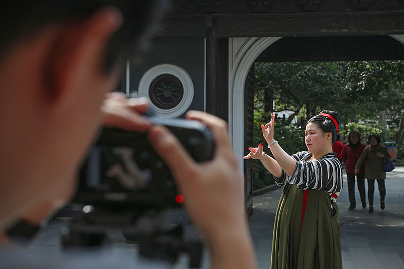 Zheng Qi models 'hanfu' for promotional images advertising her Taobao shop at a garden in Shanghai, March 12, 2018. Niu Jing/VCG