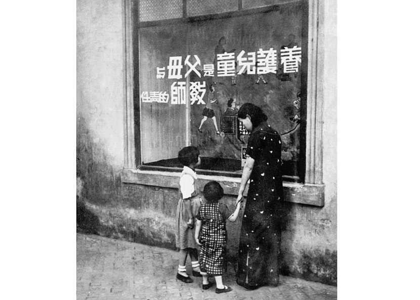 A woman and two girls gaze at a slogan in the window of a Popular Education Center in Zhenjiang, Jiangsu province, 1936. Courtesy of 'Old Photos'
