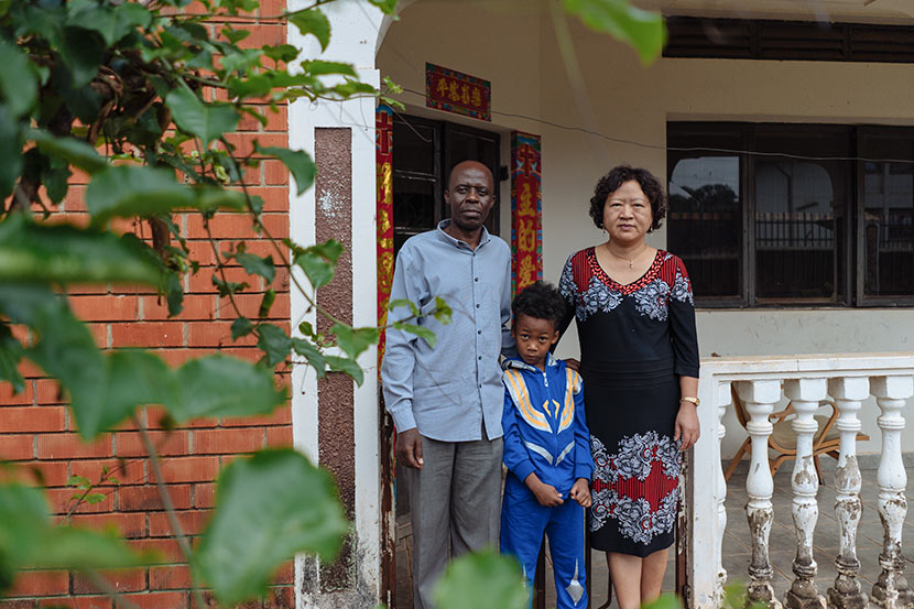 Elly Amani Gamukama (left), Yuan Zhongshun, and their son pose for a photo in front of their house in Entebbe, Uganda, March 24, 2018. Hannah Reyes Morales for Sixth Tone