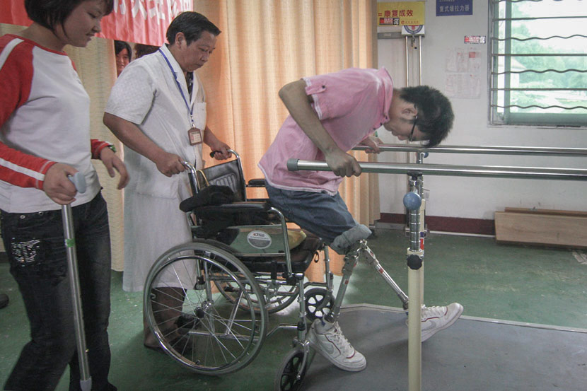 Zheng Haiyang attempts to stand on prosthetic legs during rehabilitation in Mianyang, Sichuan province, May 8, 2009. Guo Guoquan/IC