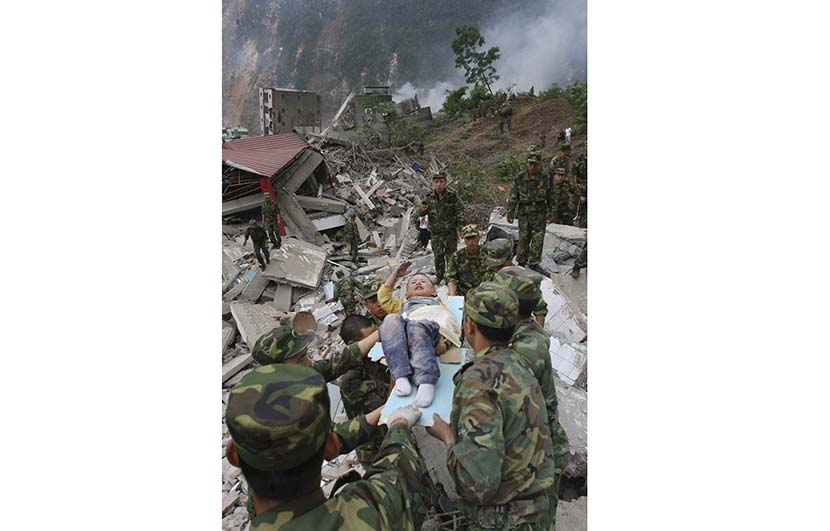 Lang Zheng, lying on a stretcher after being rescued from under a collapsed building, salutes soldiers to express his gratitude, Beichuan Qiang Autonomous County, Sichuan province, May 13, 2008. By Yang Weihua