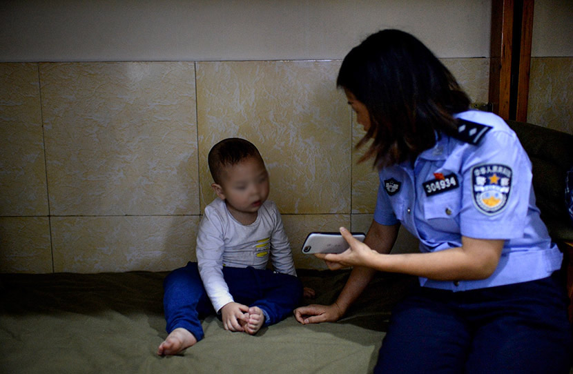 A police officer shows her mobile phone to a child abandoned by relatives at a police station in Chongqing, May 4, 2018. Chongqing Evening Post/VCG