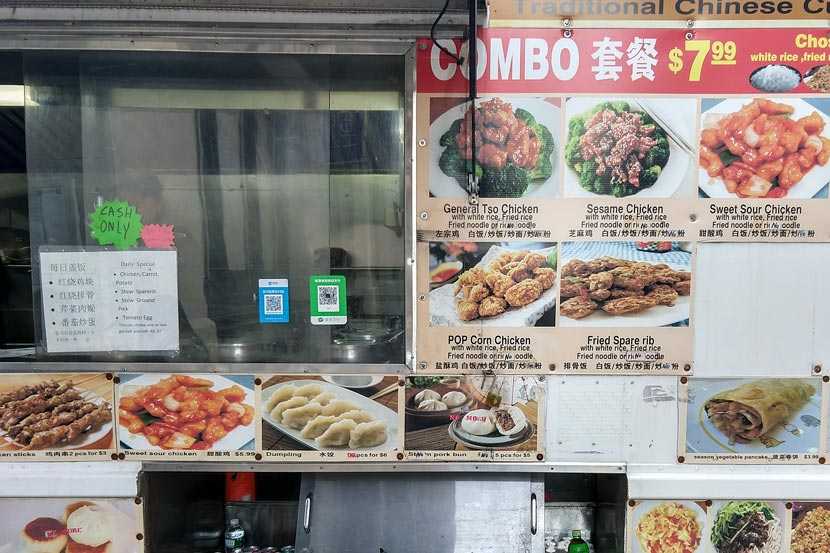 Alipay (blue) and Wechat Pay (green) QR codes are displayed on the window of a food truck near New York University, New York, April 2, 2018. Courtesy of the author