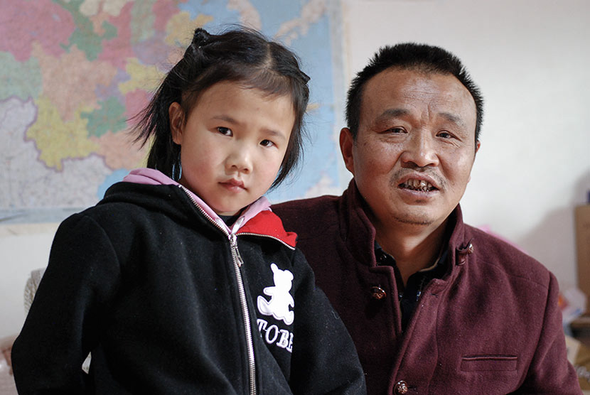 Lu Shihua poses with his 8-year-old daughter, Rui, in Piankou Township, Sichuan province, March 2018. Lu married his second wife, Duan Benju, and had Rui after the earthquake claimed the life of his 16-year-old daughter, Fang. Eileen Guo for Sixth Tone