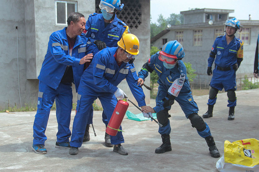 A member of Blue Sky Rescue teaches a villager to use a fire extinguisher in Baishu Village, Sichuan province, April 29, 2018. Lin Qiqing/Sixth Tone