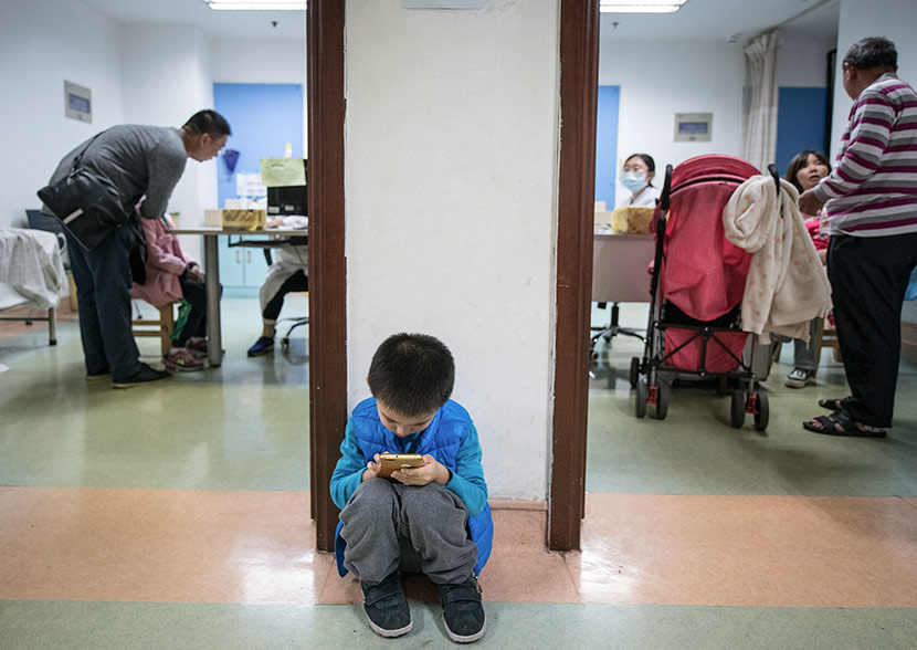 A child plays with a mobile phone while waiting to see a doctor at a hospital in Guangzhou, Guangdong province, Jan. 4, 2018. Zhang Ziwang/VCG
