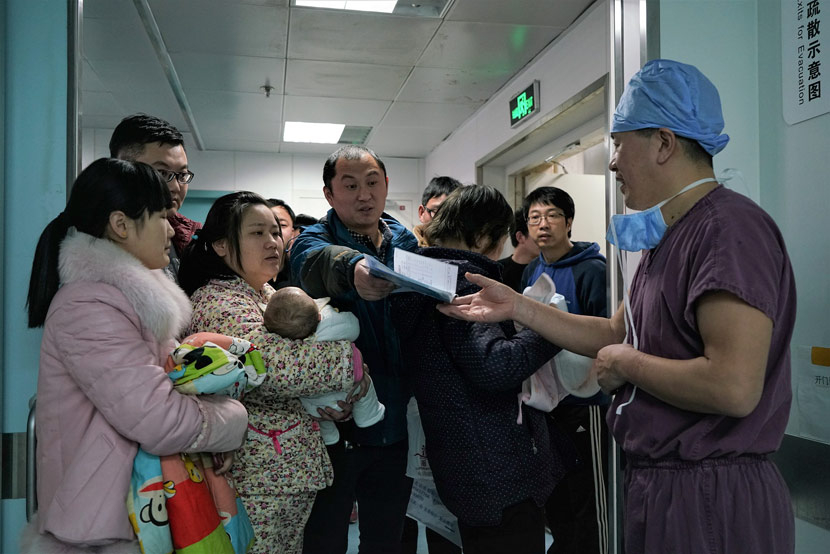 A pediatrician receives medical records from a sick child's father at a hospital in Beijing, March 12, 2018. Cai Yingli/Caixin/VCG