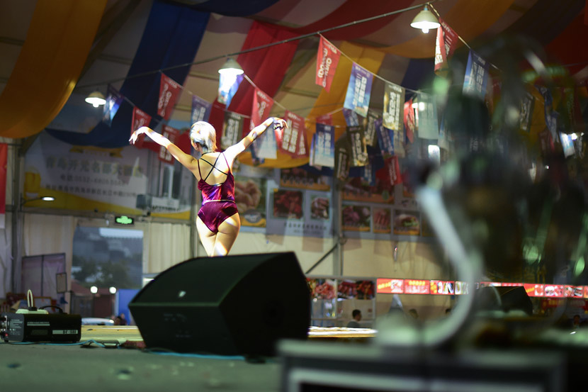 A woman performs inside a tent at a night market in Qingdao, Shandong province, Aug. 10, 2017. VCG