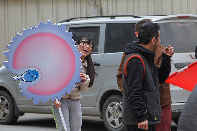 A woman holds a sign showing an egg and sperm in Zhengzhou, Henan province, March 23, 2016. IC