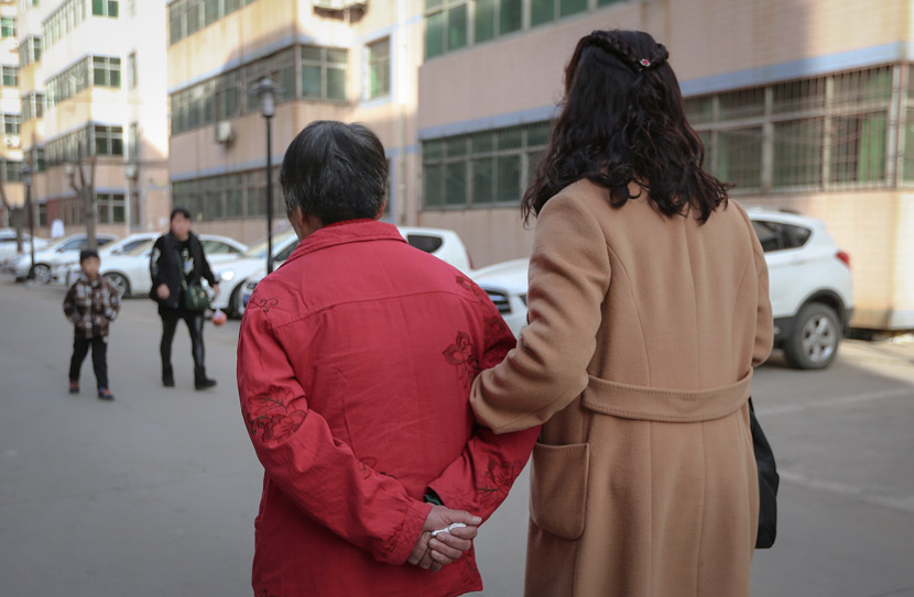 A woman and her elderly mother take a walk in Xi'an, Shaanxi province, Feb. 24, 2018. VCG