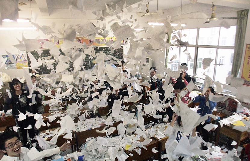 Students throw their study materials into the air after completing their college entrance exams in Xiangyang, Hubei province, June 8, 2010. Li Xi/VCG