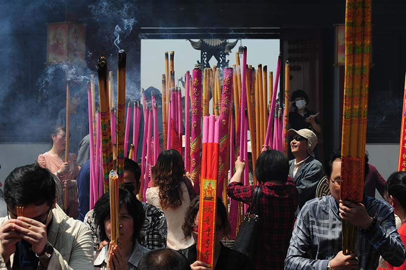 Parents pray and burn incense to bring their children good luck on the college entrance exams in Nantong, Jiangsu province, May 13, 2013. Chen Feng/VCG