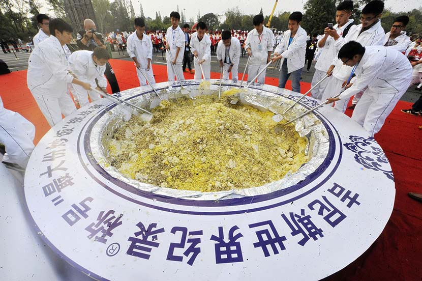 Cooks attempt to set the Guinness World Record for the largest serving of egg fried rice in Yangzhou, Jiangsu province, Oct. 22, 2015. Meng Delong/VCG