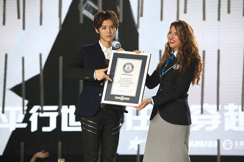 Lu Han (left) receives the Guinness World Record award for most comments on a social media post in Beijing, Sept. 25, 2015. VCG