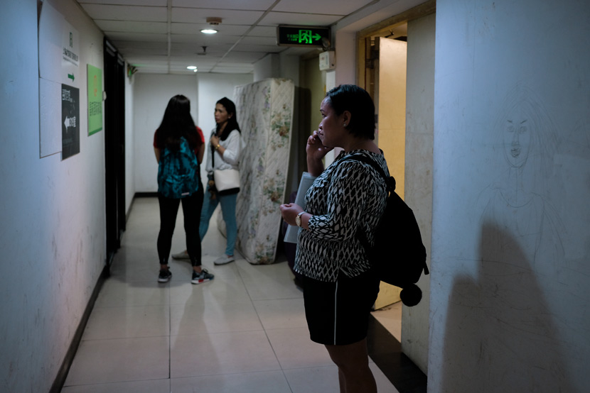 Lalaine Siason talks on her mobile phone while waiting outside the 'ayi' agency in Shanghai, May 31, 2018. Many such agencies are located in run-down residential properties. Nicole Lim for Sixth Tone