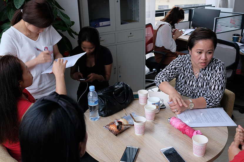 Lalaine Siason and four undocumented Filipina workers discuss the details of an employment contract with an 'ayi' agency in Shanghai, May 31, 2018. Nicole Lim for Sixth Tone