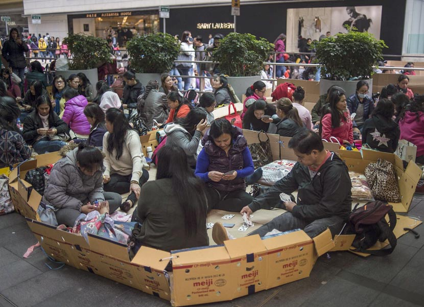 Filipina workers sit on cardboard boxes playing cards on their day off in Hong Kong, Feb. 18, 2018. Andrew Caballero-Reynolds/VCG