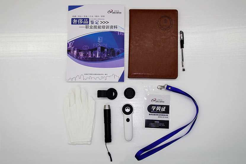 Gloves, flashlight, magnifying glass, textbook, and notebook are neatly arranged on a desk before the luxury good appraisal class in Beijing, May 17, 2018. Courtesy of the Luxury Appraisal Center