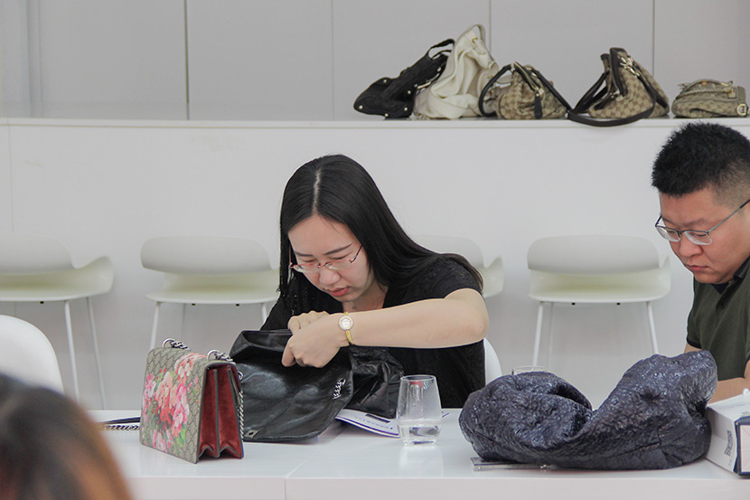 Peng Jingjing, seated next to her husband, examines a secondhand bag during a class organized by the Luxury Appraisal Center in Beijing, May 19, 2018. Courtesy of the Luxury Appraisal Center