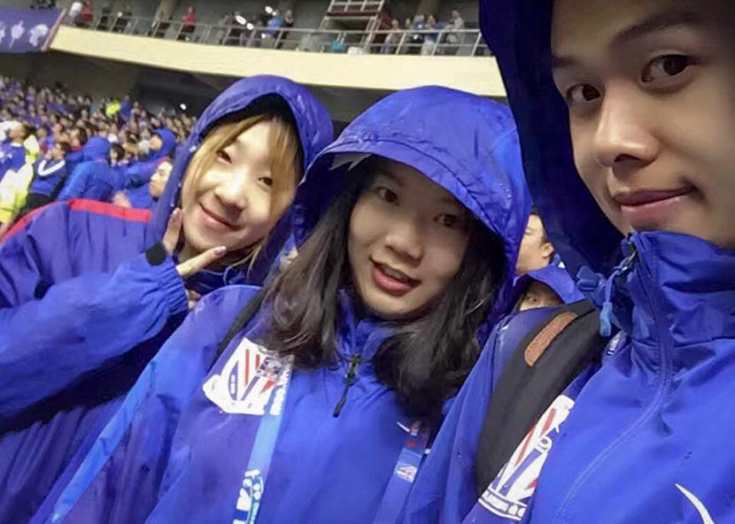 Qian Danlu (center) braves the rain to watch a soccer game in Shanghai, 2016. Courtesy of Qian Danlu