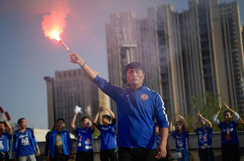 Sun Zhidong rises a firecracker before a soccer match in Yinchuan, Ningxia Hui Autonomous Region, April 25, 2018. Chen Bo/IC