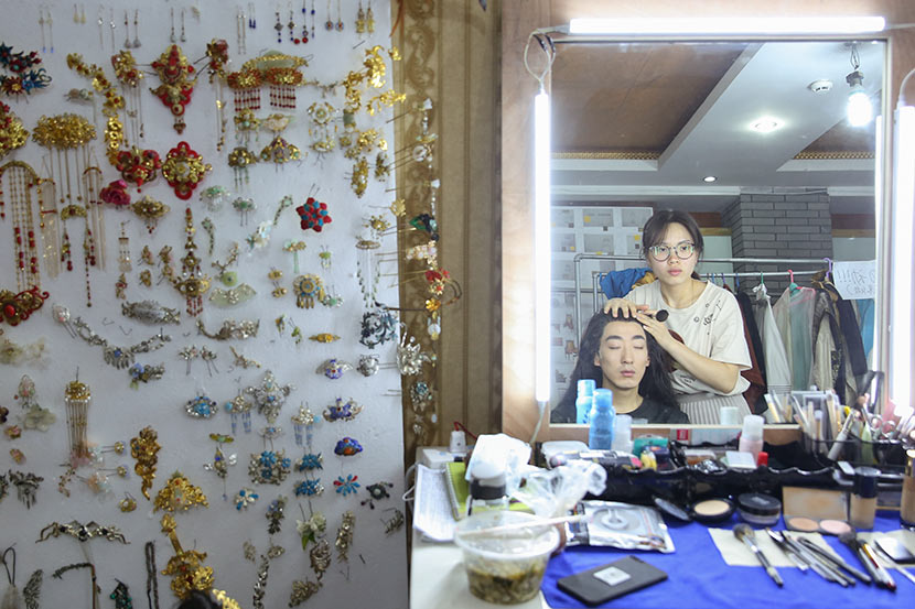 A makeup artist powders Peng Yusi's face at a dressing room in Hengdian Town, Zhejiang province, May 26, 2018. Shi Yangkun/Sixth Tone