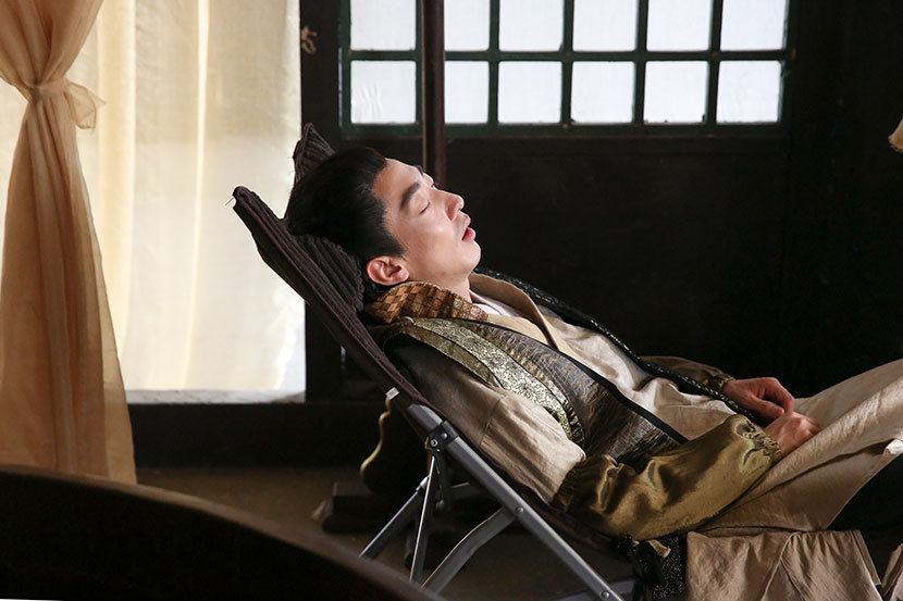 Peng Yusi takes a nap at a film set in Hengdian Town, Zhejiang province, May 26, 2018. Shi Yangkun/Sixth Tone