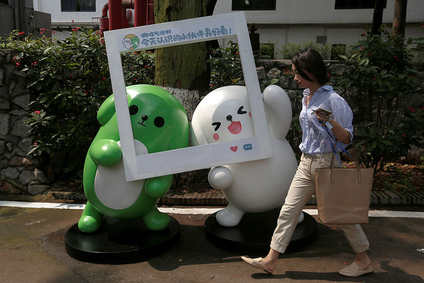 A woman walks past WeChat mascots outside the Tencent office in Guangzhou, Guangdong province, May 9, 2017. Bobby Yip/Reuters/VCG