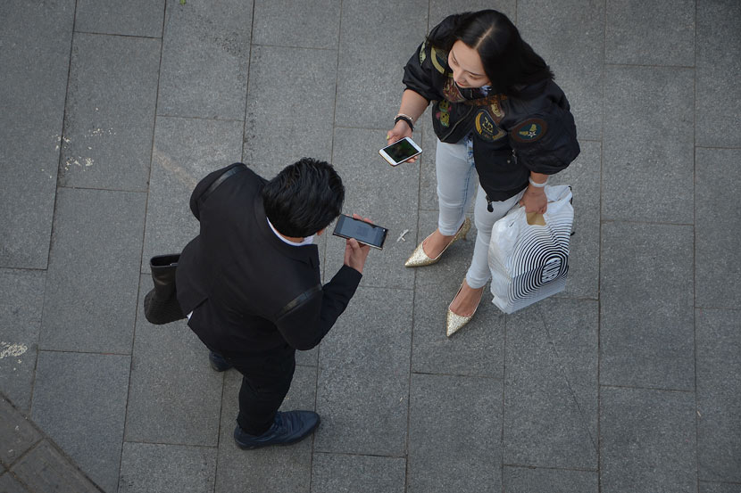 WeChat users exchange their personal QR codes in Xi'an, Shaanxi province, March 7, 2015. Lei Jia/VCG