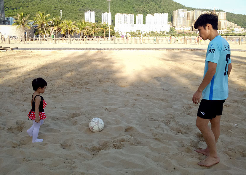 Deng Shiping kicks a ball around with his daughter in Zhabo Town, Guangdong province, Aug. 26, 2017. Courtesy of Deng Shiping