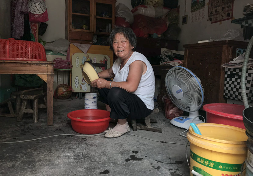 Zhao Meixia, 77, washes dishes at her home in Si County, Anhui province, June 8, 2018. Tang Xiaolan/Sixth Tone