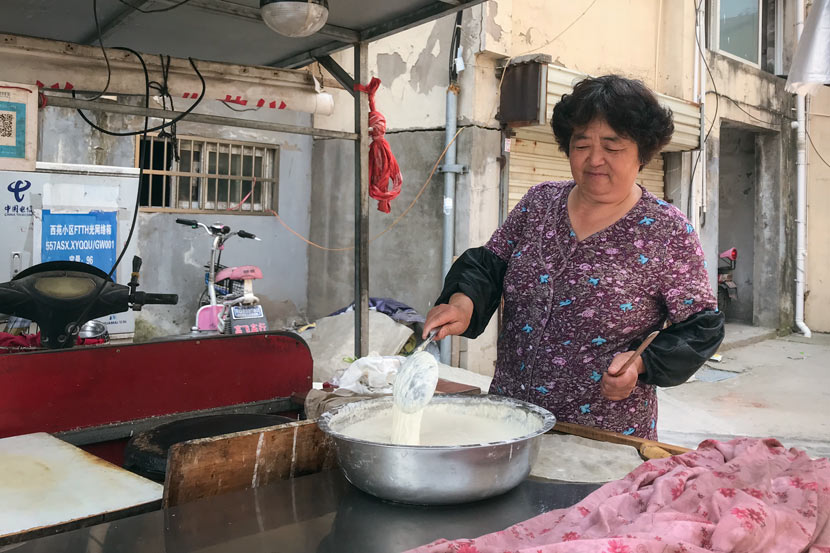Jia Zhiping cooks with water from a filtered water station in Si County, Anhui province, June 8, 2018. Tang Xiaolan/Sixth Tone