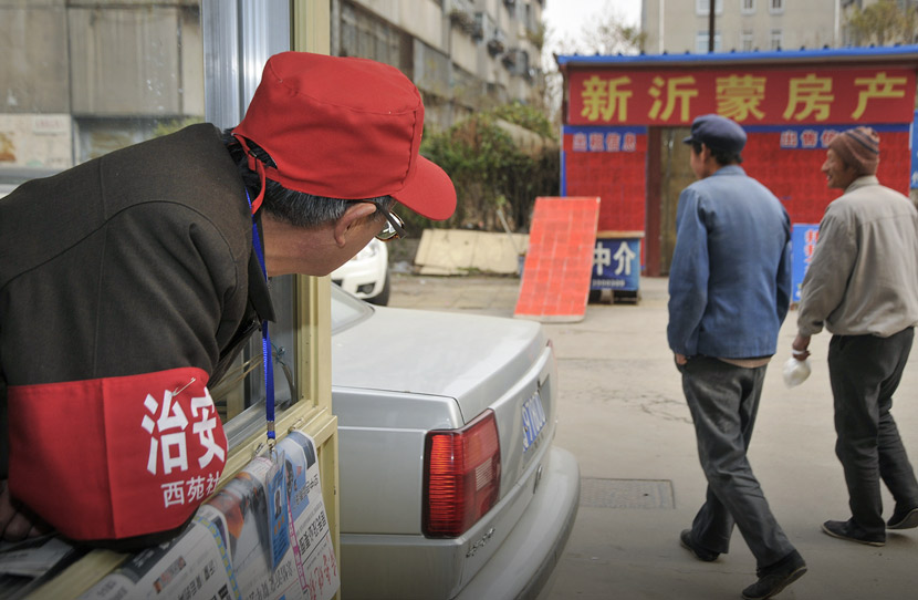 A man wearing a red armband watches passersby in Linyi, Shandong province, Dec. 15, 2009. Zhu Wutao/VCG
