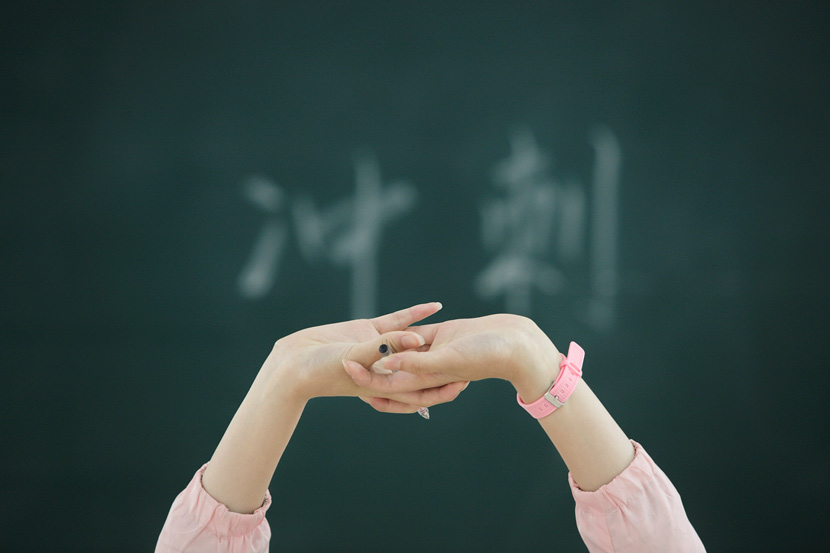A high school senior stretches in class in Nantong, Jiangsu province, May 21, 2018. The Chinese characters on the blackboard read: 'sprint.' Mao Jingsong/VCG