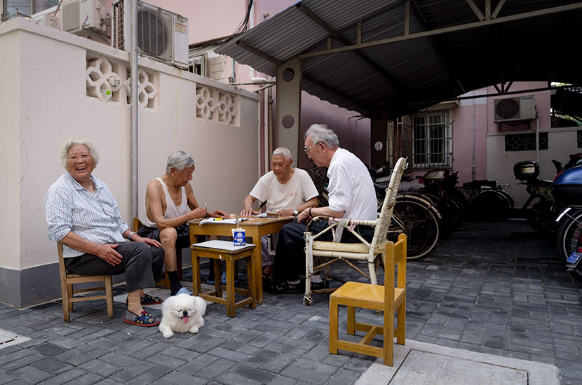 Elderly people play cards in front of Su's apartment building in Shanghai, May 14, 2018. Kevin Schoenmakers/Sixth Tone