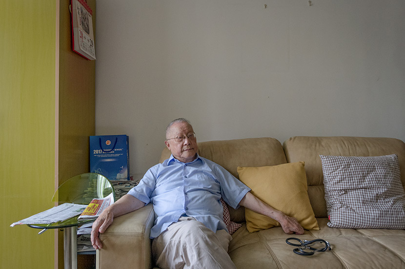 Weng Zhongyin, a retired doctor, poses for a photo in his fourth-floor apartment in Shanghai, May 14, 2018. He had just used the stethoscope to check on his wife, who has not been outside for years because she is partially paralyzed and cannot use the stairs. Kevin Schoenmakers/Sixth Tone