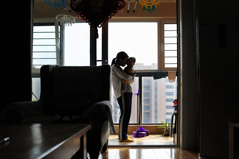 A mother holds her daughter at home in Qingdao, Shandong province, March 12, 2015. VCG