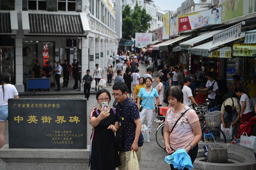 Tourists take selfies on Chung Ying Street, June 15, 2018. Fan Liya/Sixth Tone