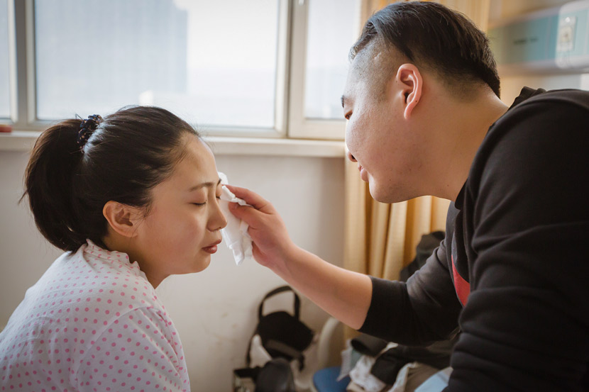 A new father wipes sweat from his wife's brow at a hospital in Taiyuan, Shanxi province, March 3, 2018. BYphoto/VCG
