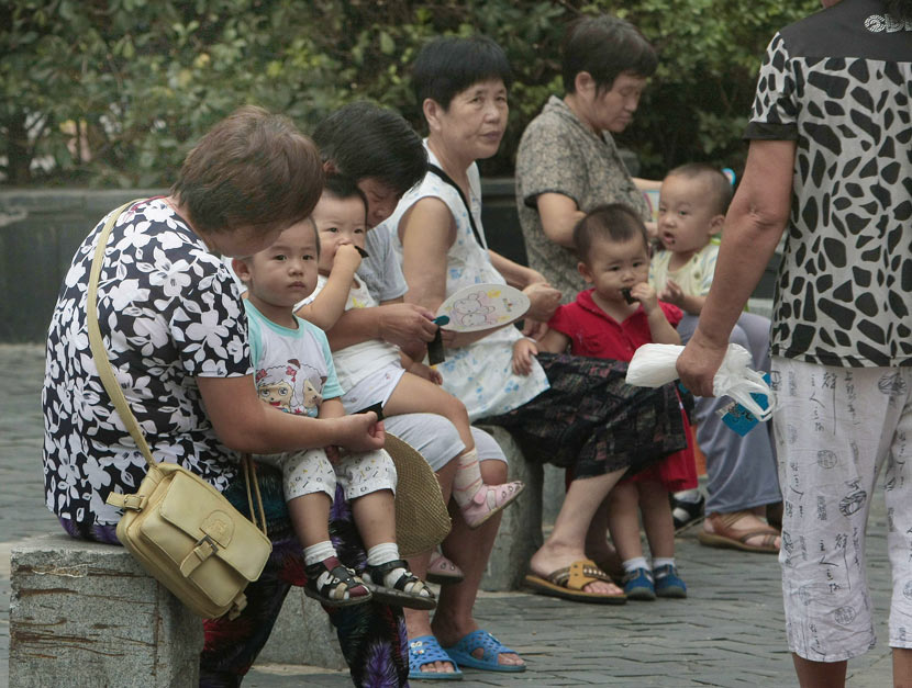 Elderly women sit with their grandchildren at a park in Nanjing, Jiangsu province, Sept. 9, 2010. An Xin/VCG