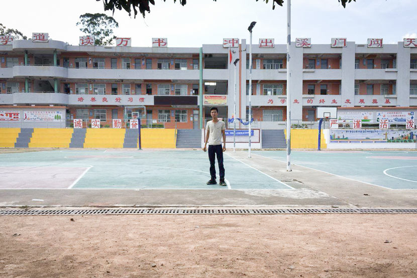 Liang Chaowei poses in front of his former school in Tangxi, Guangdong province, May 25, 2018. Courtesy of Liang Chaowei